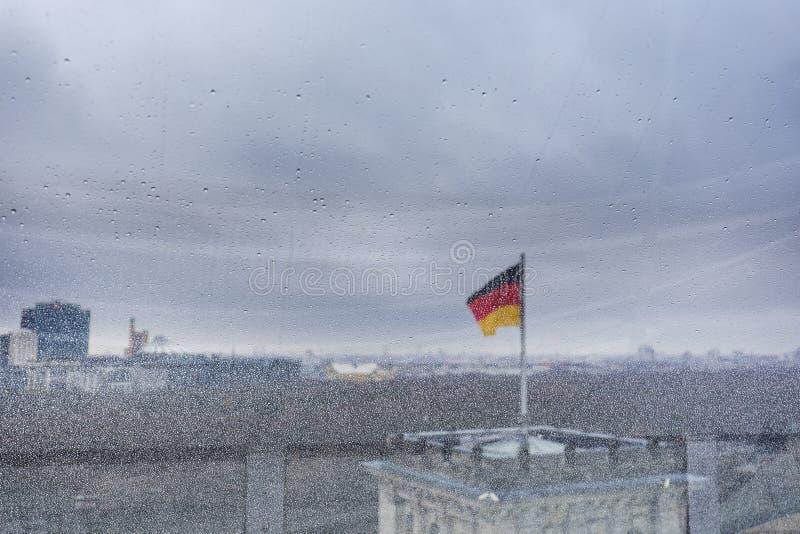 Deutsche Flagge angesehen durch ein nass Fenster lizenzfreie stockfotos