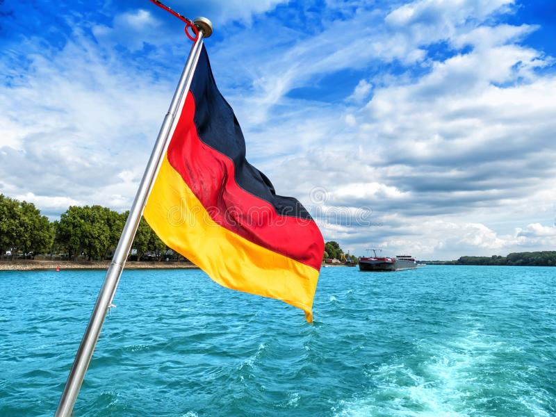 Deutsche Flagge auf dem Heck eines Schiffssegelns auf einem Fluss lizenzfreie stockfotos