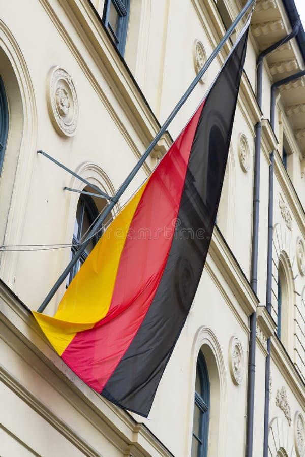 Deutsche Flagge auf dem Pfosten an der Fassade lizenzfreie stockfotos