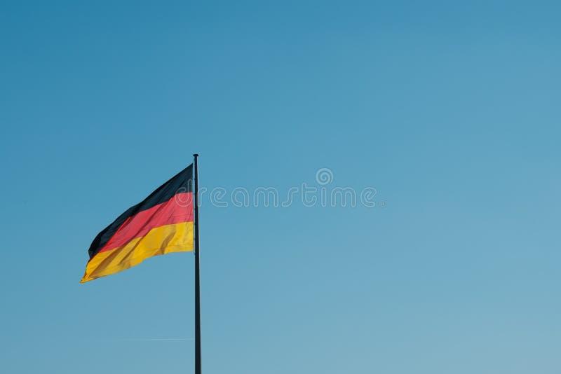Deutsche Flagge auf Pfosten auf Hintergrund des blauen Himmels mit Kopienraum stockfotografie