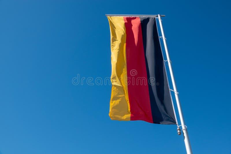 Deutsche Flagge brennt vor einem blauen Himmel durch lizenzfreies stockfoto