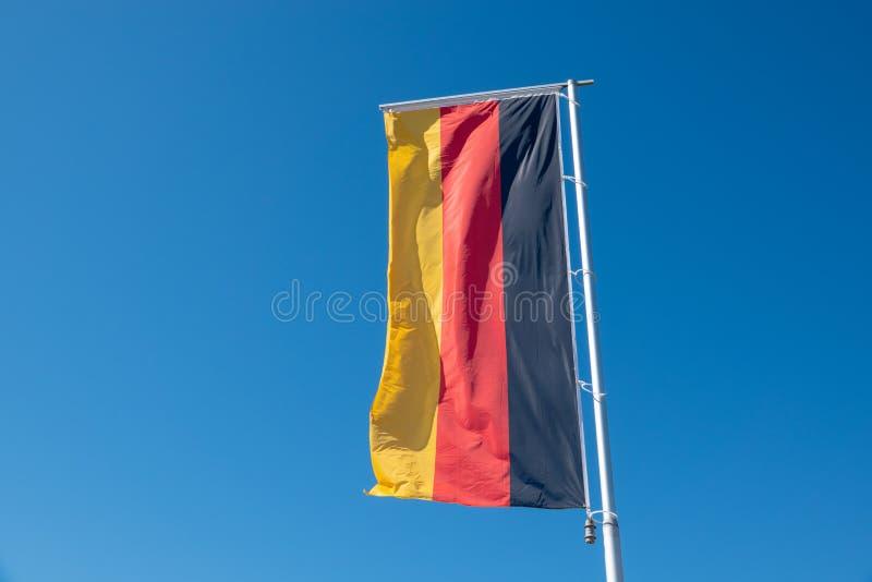 Deutsche Flagge brennt vor einem blauen Himmel durch stockbild