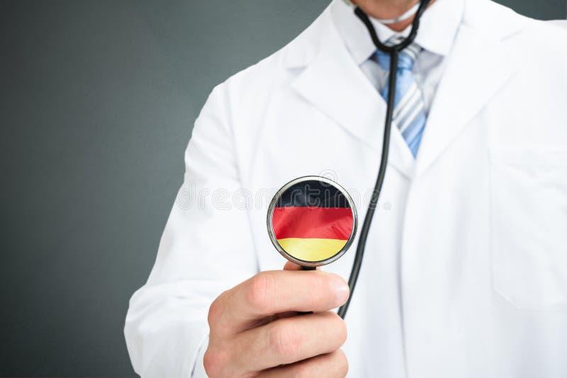 Deutsche Flagge Doktor-Holding Stethoscope With auf Chestpiece lizenzfreies stockfoto