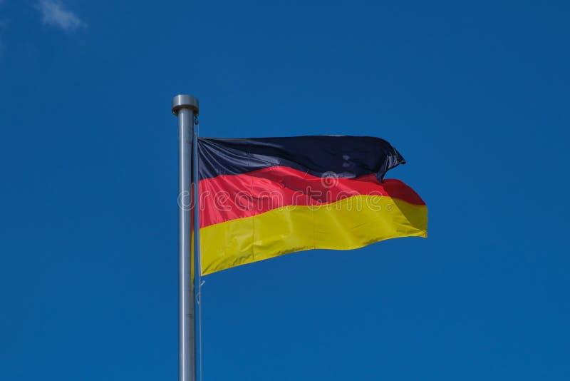 Deutsche Flagge gegen blauen Himmel lizenzfreie stockfotografie