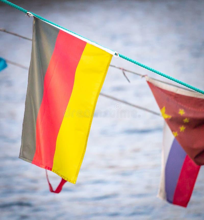 Deutsche Flagge unter anderen Flaggen stockfotografie