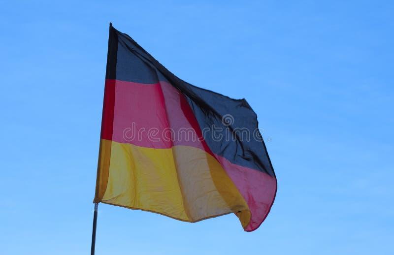 Deutsche Flagge von Deutschland über blauem Himmel stockfotos