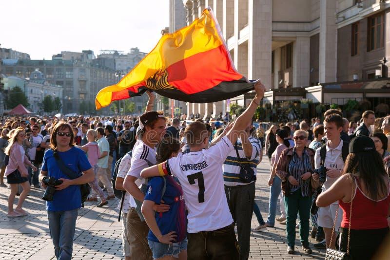 Deutsche Fußballfane mit Flagge auf rotem Quadrat Fußballweltcup stockfoto