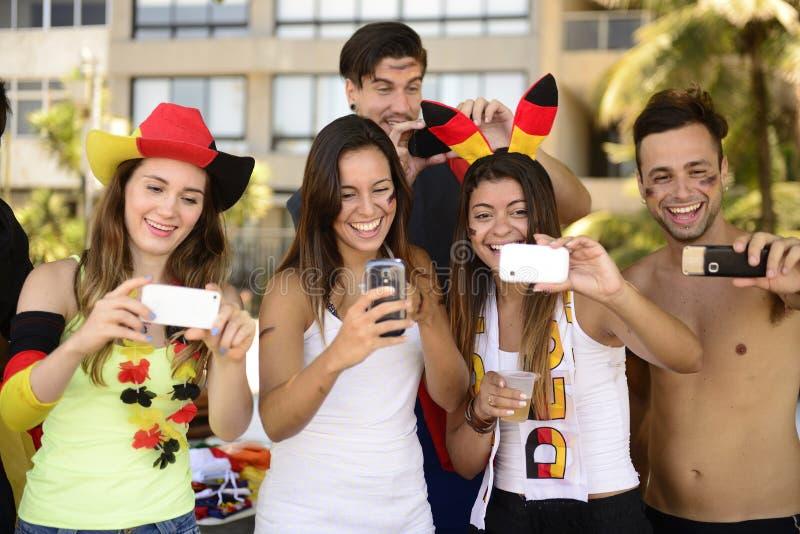 Deutsche Fußballfans, die Smartphones halten lizenzfreies stockbild