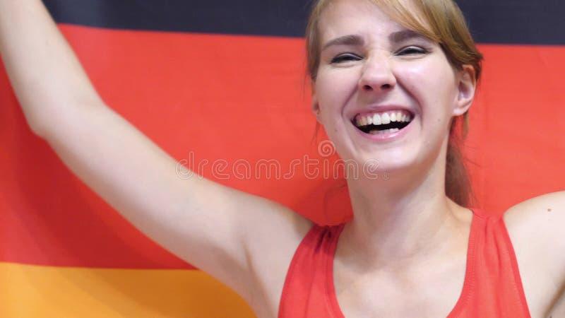 Deutsche junge feiernde Frau beim Halten der Flagge von Deutschland in der Zeitlupe stockfoto