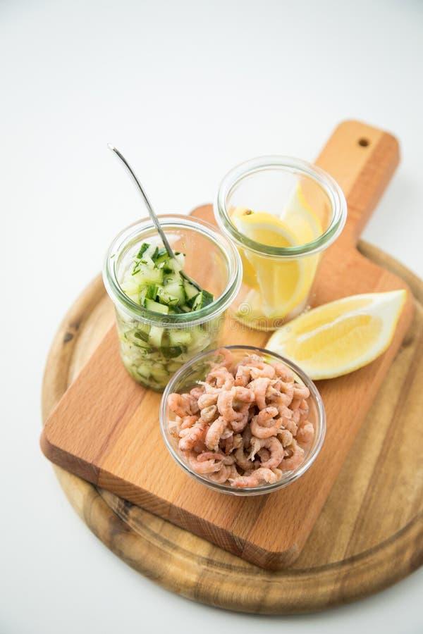 Deutsche Nordsee-Braungarnelen Frieslands in der Glasschüssel mit Gurkensalat und -zitrone auf hölzernem Brett lizenzfreie stockfotos