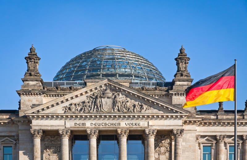 Deutsche Staatsflagge, die vor deutschem Parlament buildi wellenartig bewegt stockfotos