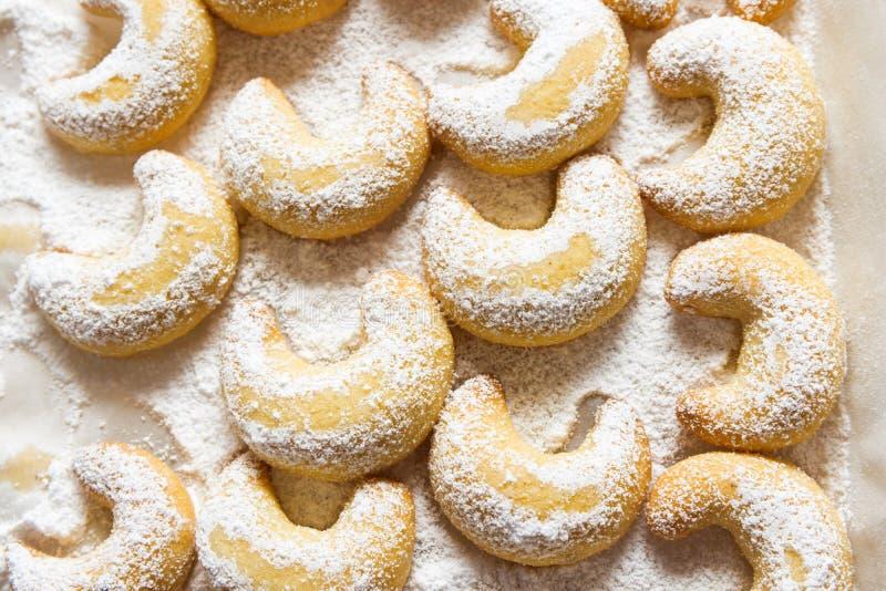 Deutsche und österreichische traditionelle Weihnachtsplätzchen-Vanillehalbmonde auf dem weißen Behälter pulverisiert mit Gießmasc lizenzfreie stockbilder