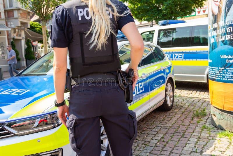 Deutsche weibliche Polizeibeamtestände vor Polizeiwagen stockfoto