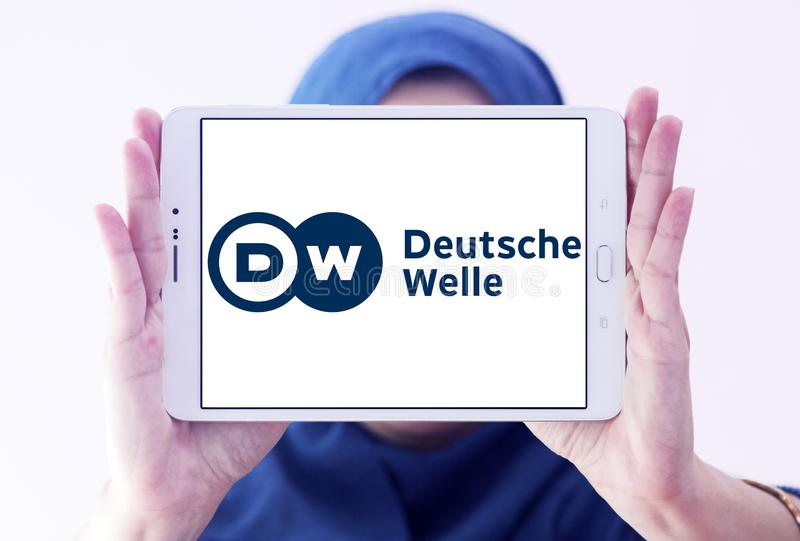Deutsche Welle broadcaster logo. Logo of Deutsche Welle broadcaster on samsung tablet holded by arab muslim woman. DW is Germany`s public international royalty free stock image