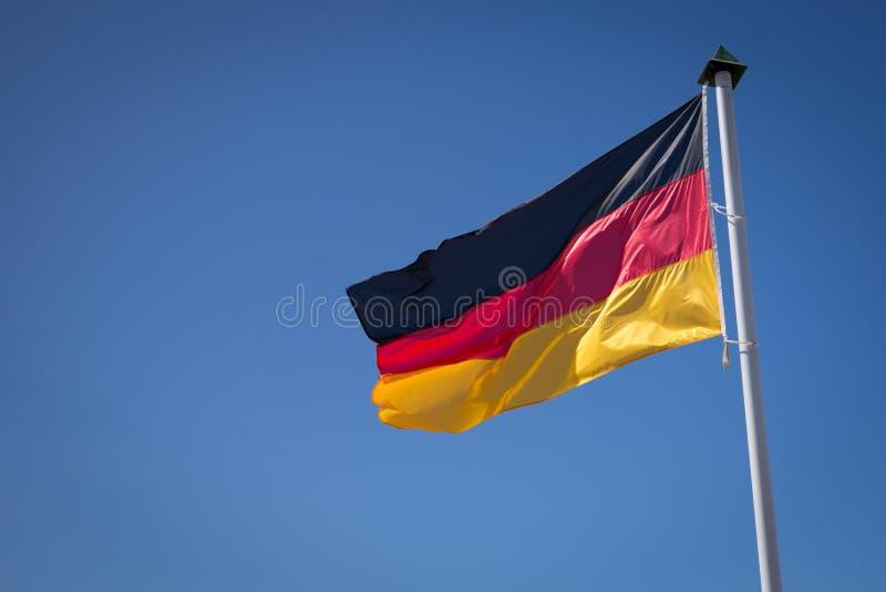 Deutsches fahnenschwenkendes gegen den blauen Himmel lizenzfreie stockbilder
