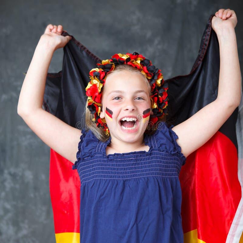 Deutsches Fußbalgebläse, das ihre Markierungsfahne wellenartig bewegt stockfotografie