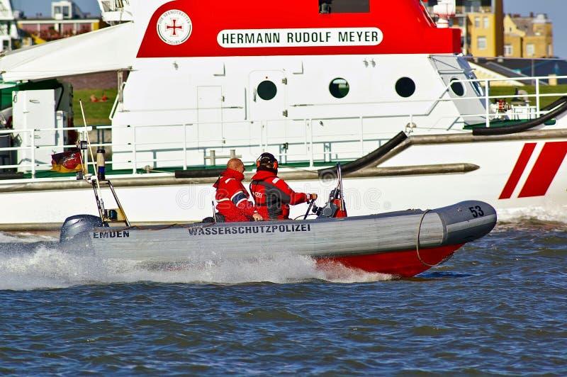 Deutsches Polizeipatrouillenboot mit zwei Polizeibeamten an Bord, die das Rettungsboot überholen stockfotografie