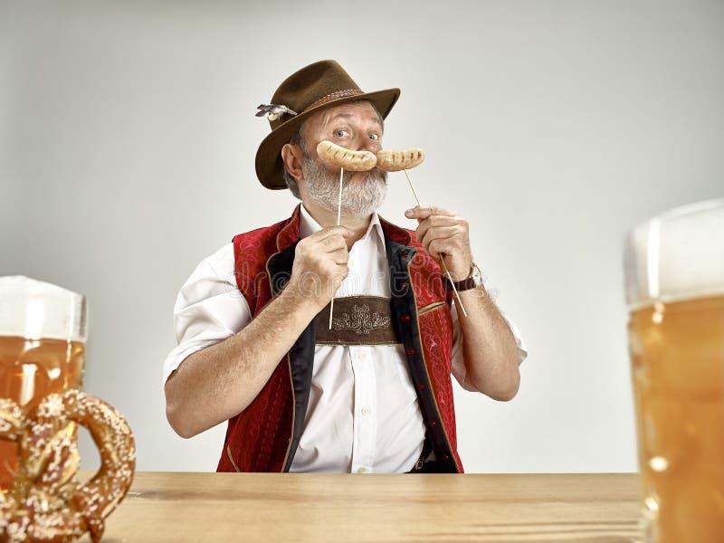 Deutschland, Bayern, oberes Bayern, Mann mit Bier kleidete im traditionellen österreichischen oder bayerischen Kostüm an stockbild