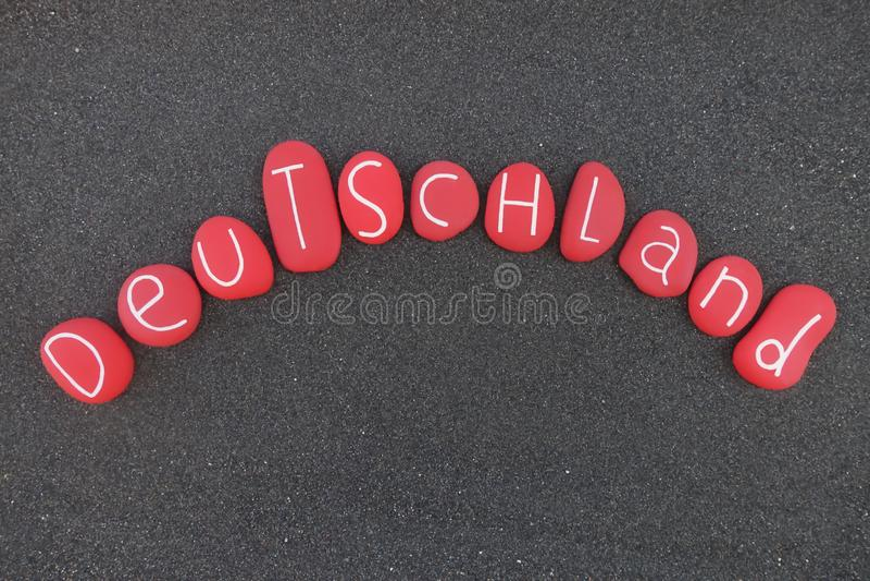 Deutschland, de naam van het land van Duitsland in duitstalig met rode geschilderde stenen over zwart vulkanisch zand stock afbeeldingen