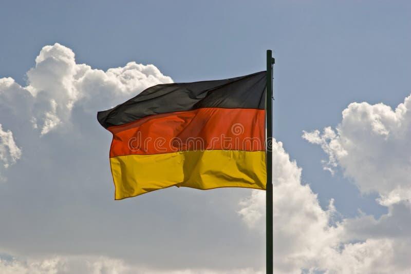 Deutschland-Flagge vor blauem Wolkenhimmel lizenzfreie stockbilder