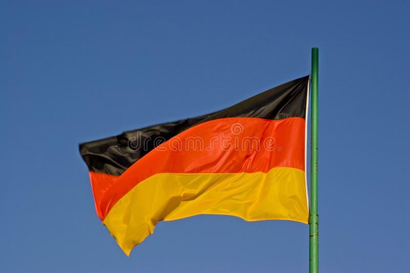 Deutschland-Flagge vor blauem Wolkenhimmel stockfotografie