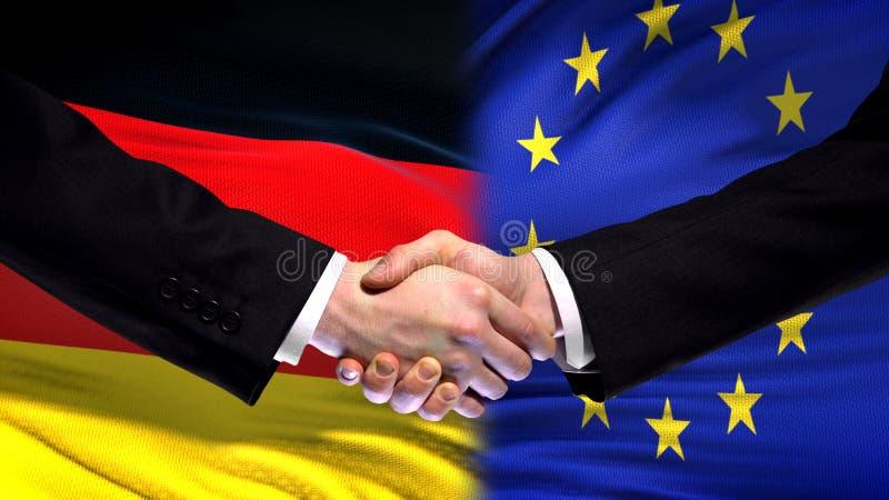 Deutschland- und Gemeinschaftshändedruck, internationale Freundschaft, Flaggenhintergrund lizenzfreie stockfotografie
