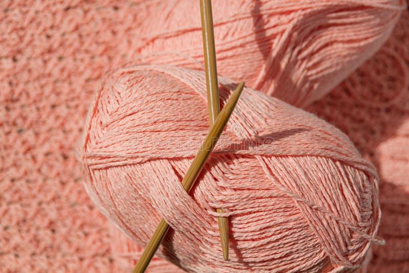 Deux écheveaux de fil de corail avec les aiguilles de tricotage circulaires en bambou sur le tissu tricoté par coton images stock