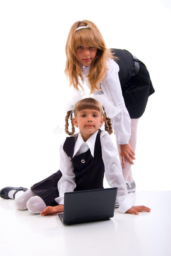 Deux écolières et ordinateurs portatifs. photos libres de droits