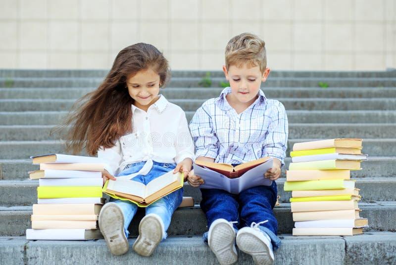 Deux écoliers ont lu des livres Le concept est de nouveau à l'école, à l'éducation, à la lecture, à l'amitié et à la famille image libre de droits