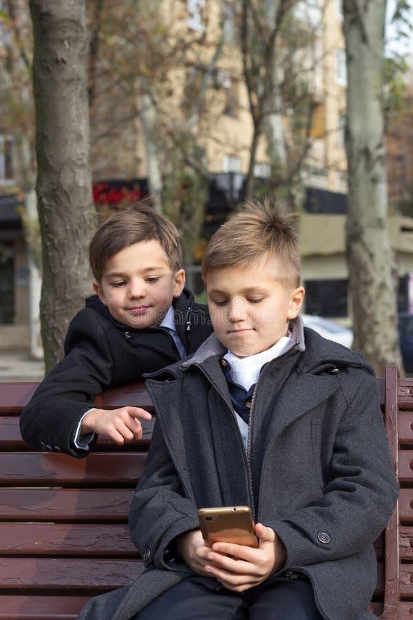 Deux écoliers regardent une vidéo intéressante sur un smartphone et sourient assis sur un banc de parc sur un photo stock
