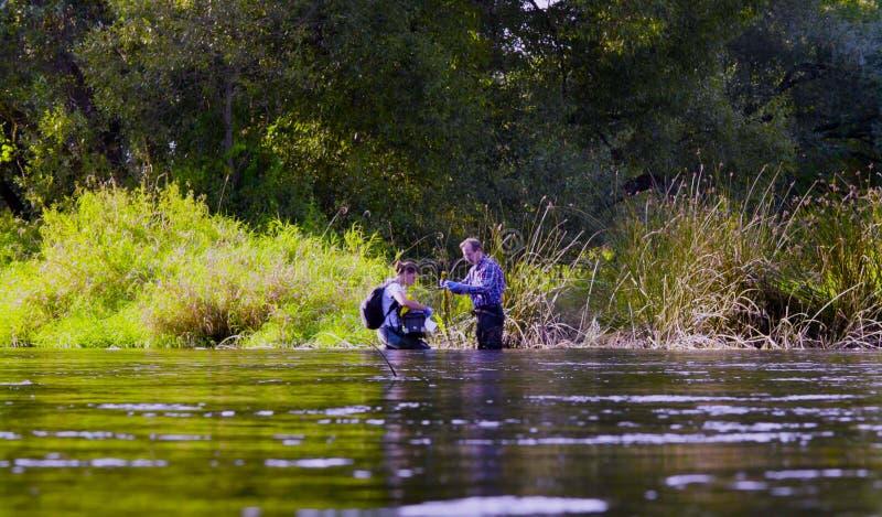Deux écologistes de scientifiques dans de hautes bottes en caoutchouc se tenant dans l'eau de la rivière de forêt photos stock