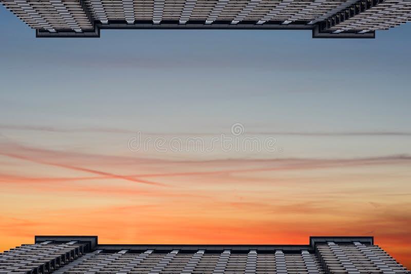 Deux édifices hauts symétriques vis-à-vis de l'un l'autre dans la perspective d'un ciel nuageux L'espace pour le texte images libres de droits