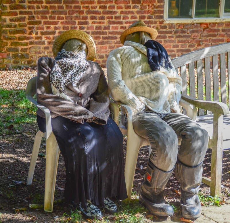 Deux épouvantails se reposant sur des chaises dehors photos libres de droits