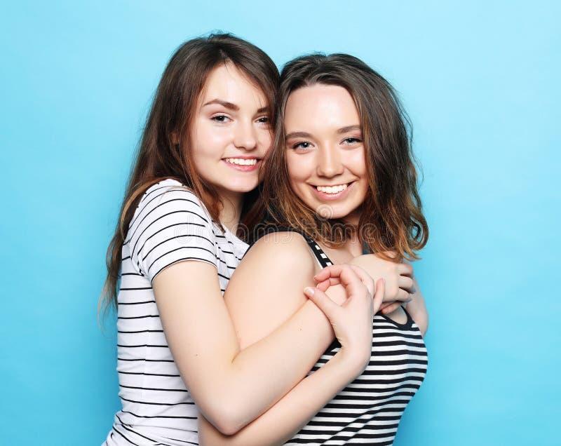 Deux étreintes d'amies assez de l'adolescence et amusements de sourire de avoir photographie stock libre de droits