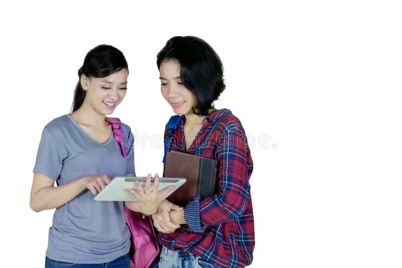 Deux étudiantes à l'aide d'un comprimé sur le studio photographie stock libre de droits
