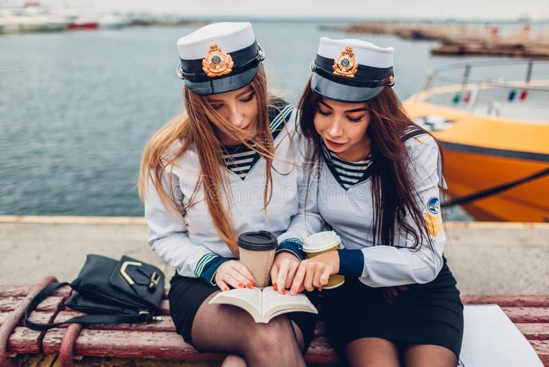 Deux étudiantes d'université de livre de lecture marin d'académie par l'uniforme de port de mer Étude d'amis photo stock