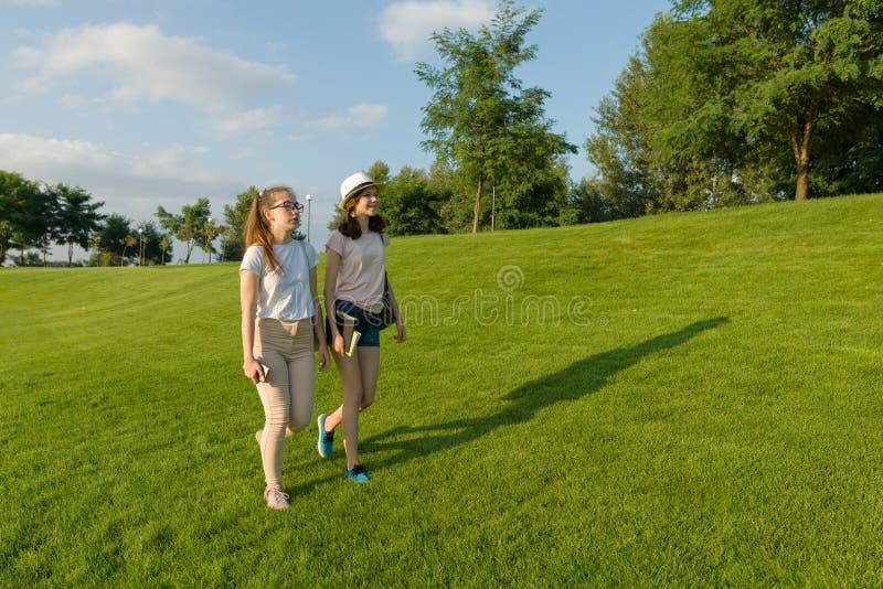 Deux étudiantes de l'adolescence avec des sacs à dos et des livres marchant sur l'herbe verte photos stock