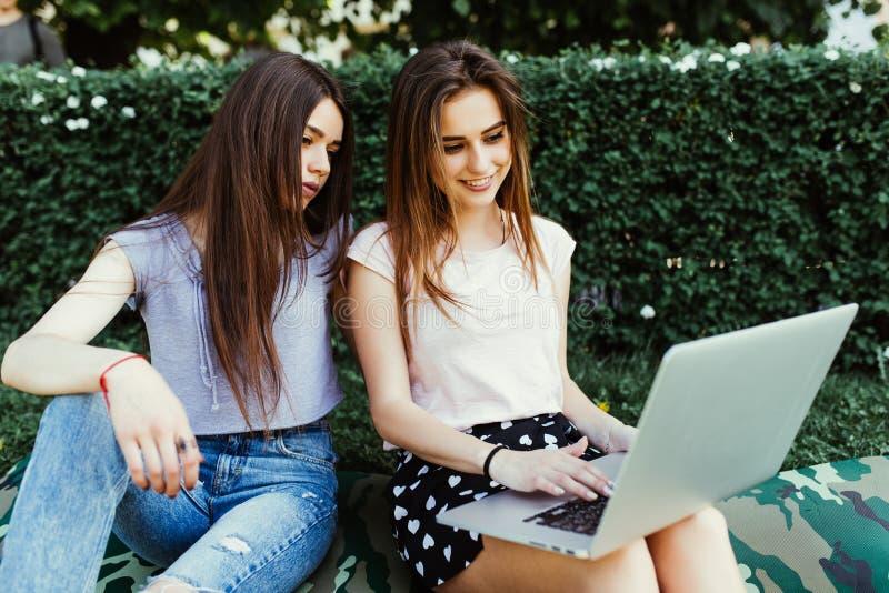 Deux étudiantes de sourire s'asseyent sur l'herbe dans la rue Ils travaillent sur l'ordinateur portable au campus image stock