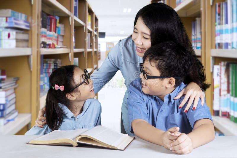 Deux étudiants élémentaires avec le professeur dans la bibliothèque images stock