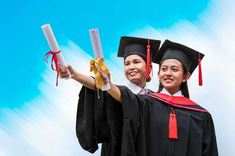 Deux étudiants asiatiques féminins dans la robe d'obtention du diplôme image stock