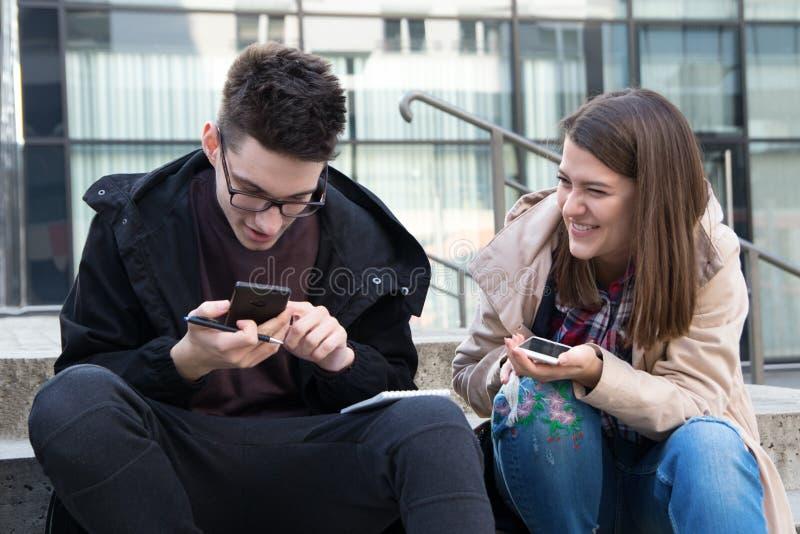 Deux étudiants avec les téléphones et le carnet intelligents photographie stock libre de droits