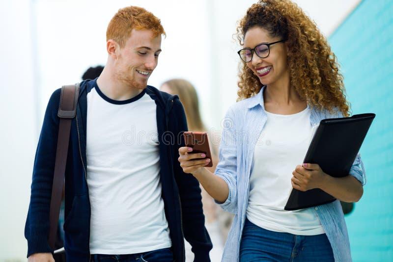 Deux étudiants employant ils téléphone portable dans une université image libre de droits