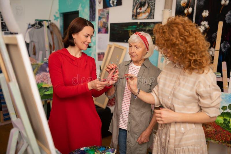 Deux étudiants et leur professeur d'art âgé tenant les palettes de peinture photos stock