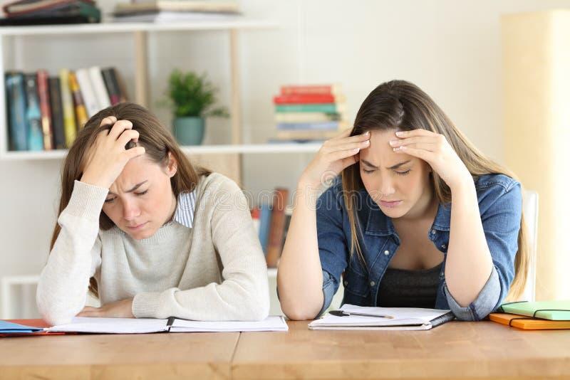 Deux étudiants fatigués étudiant dur photographie stock libre de droits