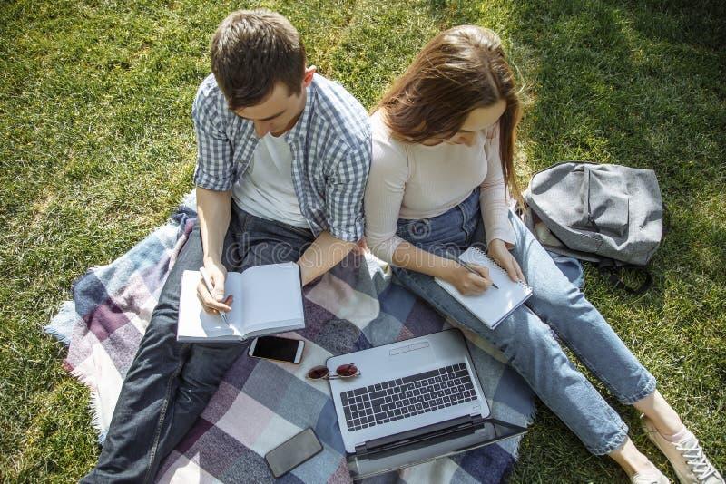 Deux étudiants font un résumé de la leçon dehors Éducation en ligne photo libre de droits