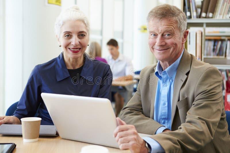 Deux étudiants mûrs travaillant ensemble dans la bibliothèque utilisant l'ordinateur portable photo stock