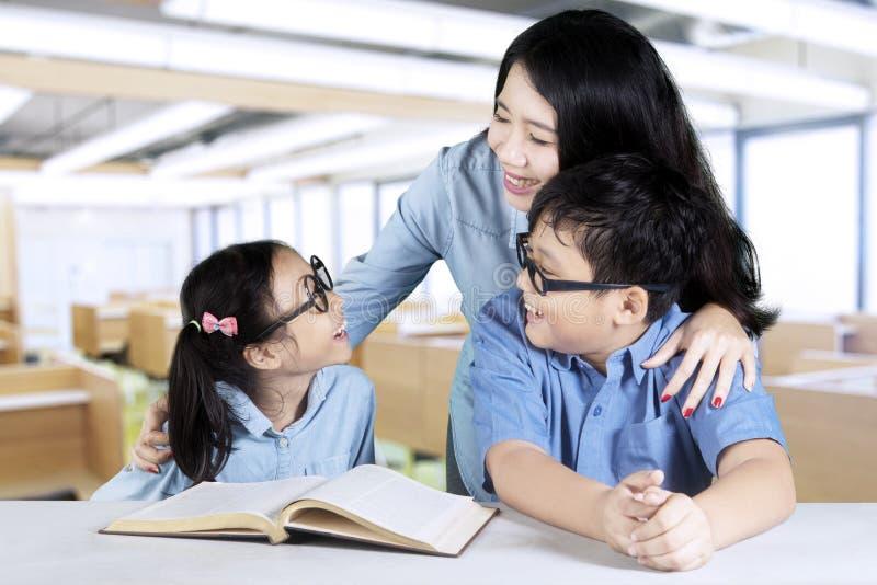 Deux étudiants parlant avec leur tuteur dans la classe image stock