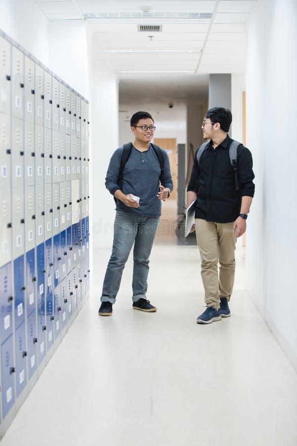 Deux étudiants se tiennent à côté des casiers et parlent ensemble en bas du hall d'école photographie stock libre de droits