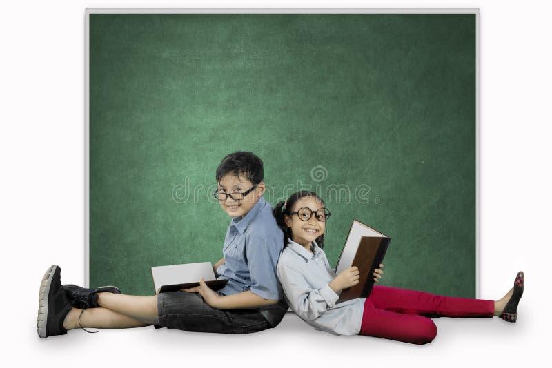 Deux étudiants tenant un livre dans le studio photos libres de droits