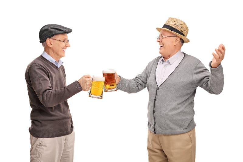 Deux aînés gais buvant de la bière images stock